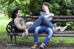 Pares, muchacho precioso y muchacha jovenes sentándose en un talkin del banco de parque foto de archivo libre de regalías