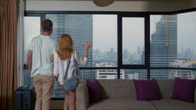 Pares, mujer y hombre atractivos con una maleta en el fondo de rascacielos en una ventana panorámica por la tarde almacen de metraje de vídeo