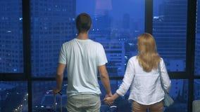 Pares, mujer y hombre atractivos con una maleta en el fondo de rascacielos en una ventana panorámica por la tarde almacen de video