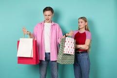Pares, mulher e homem bonitos novos na roupa ocasional isolada sobre o fundo azul fotos de stock