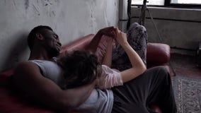 Pares multiétnicos hermosos en pijamas en el sofá rojo Demostración de la mujer algo servir, señalando con el finger Cámara lenta metrajes
