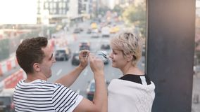 Pares multiétnicos jovenes casuales que se sientan en un puente sobre la calle de Nueva York que tiene lentes de la diversión, de almacen de video
