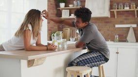 Pares multiétnicos jovenes que hablan por la mañana por la tabla en la cocina Individuo hermoso que tiene hoja del putting green  almacen de metraje de vídeo