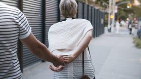 Pares multiétnicos románticos jovenes felices que corren a lo largo de las calles de New York City juntas que celebran las manos  almacen de video