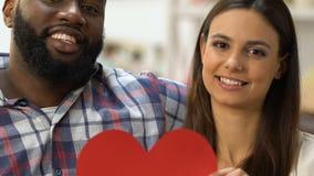 Pares multi-étnicos atrativos que mostram o coração de papel grande que senta-se no sofá no plano video estoque