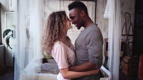 Pares multi-étnicos bonitos nos pijamas que dançam junto e que sorriem Homem e mulher que têm o divertimento Movimento lento filme