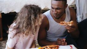 Pares multi-étnicos com fome que comem a pizza O homem e a mulher alimentam cada outro, têm o divertimento durante a refeição com filme
