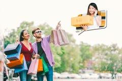 pares Multi-étnicos com saco de compras, proprietário empresarial pequeno novo do ponto do homem, bens da venda na chamada de tel imagem de stock royalty free