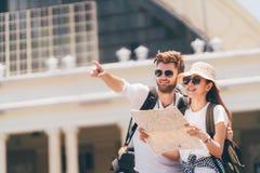 Pares multi-étnicos do viajante usando o mapa local genérico junto no dia ensolarado Viagem da lua de mel, turista do mochileiro,