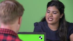 Pares multi-étnicos jovenes del negocio junto contra fondo verde almacen de video