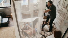 Pares multi-étnicos no photoshoot Registros do fotógrafo video durante o homem e a mulher que encontram-se na cama, smartphone do video estoque