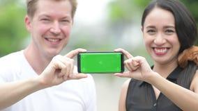 Pares multi-étnicos novos que mostram o telefone junto nas ruas fora video estoque