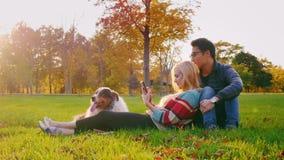 Pares multi-étnicos novos que relaxam no parque com seu cão A mulher caucasiano aprecia a tabuleta, um homem coreano senta-se pró filme