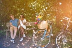 Pares multi-étnicos novos que têm um passeio da bicicleta na natureza Foto de Stock Royalty Free