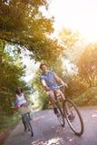 Pares multi-étnicos novos que têm um passeio da bicicleta na natureza Imagens de Stock