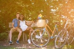 Pares multi-étnicos novos que têm um passeio da bicicleta na natureza Imagem de Stock Royalty Free