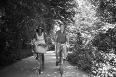 Pares multi-étnicos novos que têm um passeio da bicicleta na natureza Fotografia de Stock