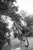 Pares multi-étnicos novos que têm um passeio da bicicleta na natureza Fotografia de Stock Royalty Free