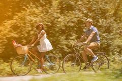 Pares multi-étnicos novos que têm um passeio da bicicleta na natureza Fotos de Stock Royalty Free