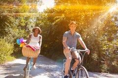 Pares multi-étnicos novos que têm um passeio da bicicleta na natureza Foto de Stock