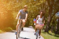 Pares multi-étnicos novos que têm um passeio da bicicleta na natureza Imagens de Stock Royalty Free