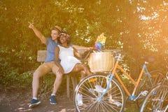Pares multi-étnicos novos que têm um passeio da bicicleta na natureza Imagem de Stock