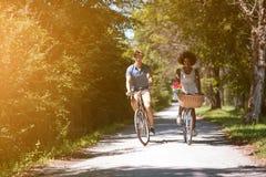 Pares multi-étnicos novos que têm um passeio da bicicleta na natureza Fotos de Stock