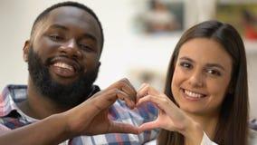 Pares multi-étnicos sonrientes que hacen el corazón con las manos, símbolo de su amor metrajes