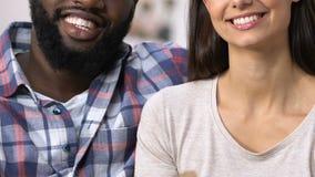 Pares multi-étnicos sonrientes que sostienen el carro de bebé de la cartulina, planeamiento del embarazo almacen de metraje de vídeo