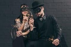 pares multiculturais em máscaras do Natal com vidros do tinido dos sparkles Imagens de Stock
