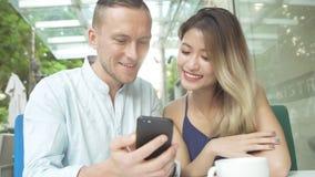 Pares multiculturales usando el app en smartphone junto Foto de archivo libre de regalías