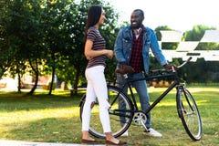 pares multirraciais de sorriso com a bicicleta retro que tem a conversação imagem de stock royalty free