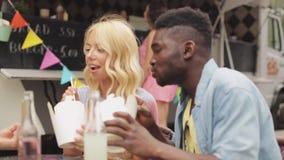 Pares multirraciais felizes que comem o frigideira chinesa no caminhão do alimento video estoque