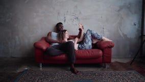 Pares multirraciales cariñosos en el sofá rojo Mujer que juega con la palma del hombre s, las manos del control y el laught Cámar metrajes