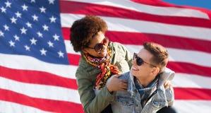 Pares multirraciales felices sobre bandera americana Fotografía de archivo