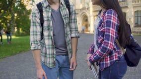 Pares multirraciales que abrazan y que hablan cerca de la universidad, amor del estudiante, encontrándose metrajes