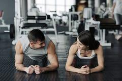 Pares musculares jovenes que hacen haciendo entrenamiento duro en el gimnasio Hacer el tabl?n en el gimnasio imagen de archivo