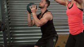 Pares musculares que hacen ejercicio de la bola almacen de metraje de vídeo