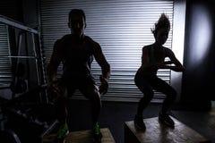 Pares musculares que hacen posiciones en cuclillas de salto foto de archivo libre de regalías