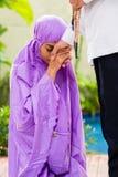 Pares musulmanes asiáticos, hombre y mujer, rogando en casa Imagenes de archivo