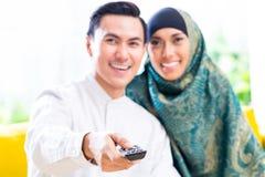 Pares musulmanes asiáticos que cambian la TV con teledirigido Foto de archivo libre de regalías