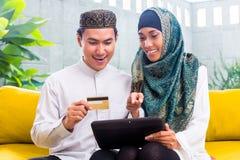 Pares musulmanes asiáticos que hacen compras en línea en el cojín en sala de estar Foto de archivo libre de regalías