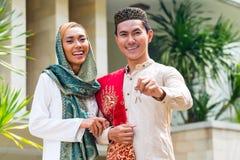 Pares musulmanes asiáticos que llevan el vestido tradicional Imagen de archivo libre de regalías