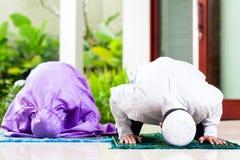 Pares musulmanes asiáticos, hombre y mujer, rogando en casa Foto de archivo libre de regalías