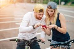 Pares na bicicleta que olha o telefone Homem e mulher na viagem por estrada usando o telefone celular foto de stock royalty free