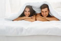 Pares na cama sob a cobertura Foto de Stock Royalty Free