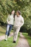 Pares na caminhada ao longo do trajeto da floresta Fotografia de Stock Royalty Free
