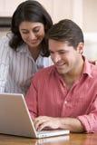 Pares na cozinha com documento usando o portátil Fotografia de Stock