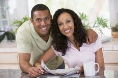 Pares na cozinha com jornal com um café imagens de stock royalty free