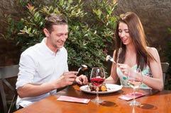 Pares na data que aprecia o deserto e o vinho no terraço Fotografia de Stock